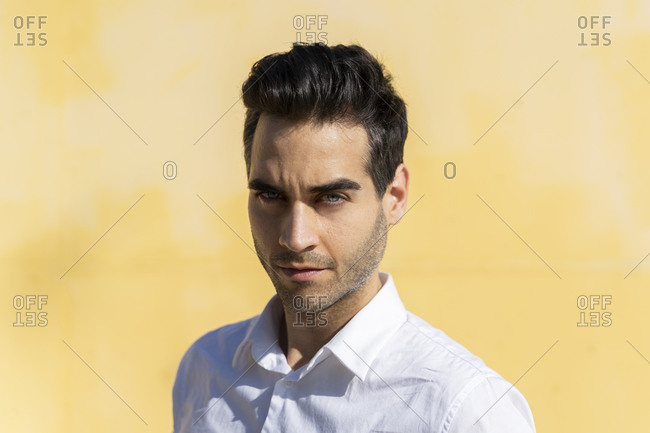 Portrait of handsome businessman against yellow wall