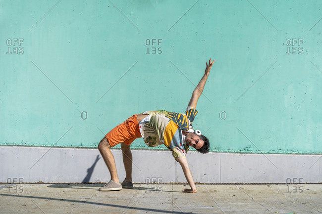 Casual man performing acrobatics in front of green wall