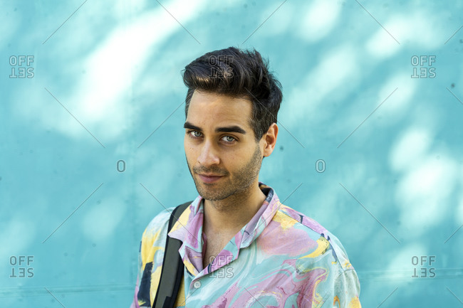 Attractive man standing in front of blue wall- portrait
