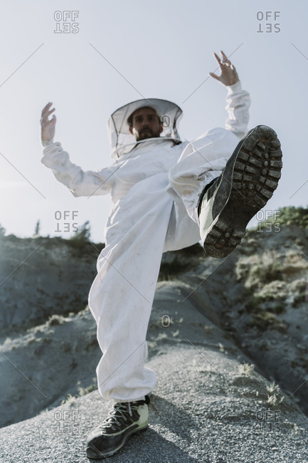 Man wearing a beekeeper dress stepping in a dry apocalyptical landscape