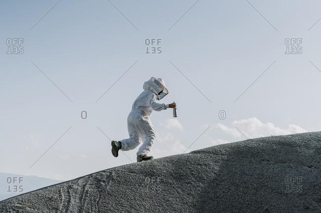 Man wearing a beekeeper dress stepping on a hill