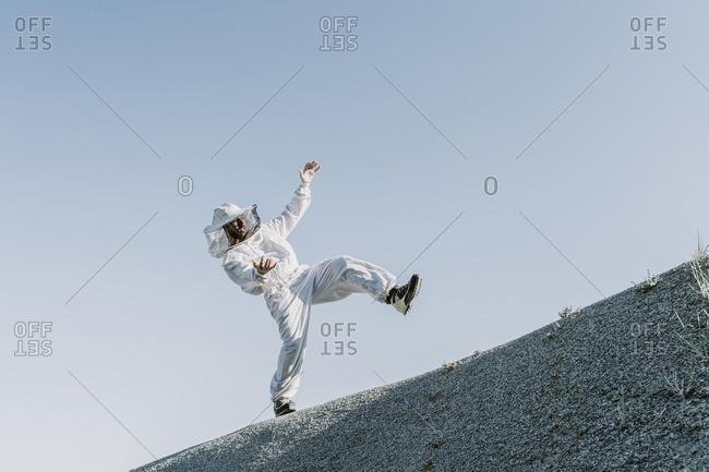 Man wearing a beekeeper dress tumbling on a hill