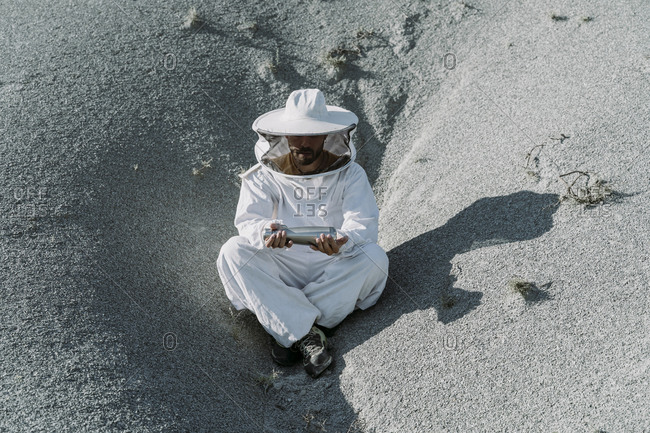 Man wearing a beekeeper dress sitting in a dry apocalyptical landscape holding thermos flask