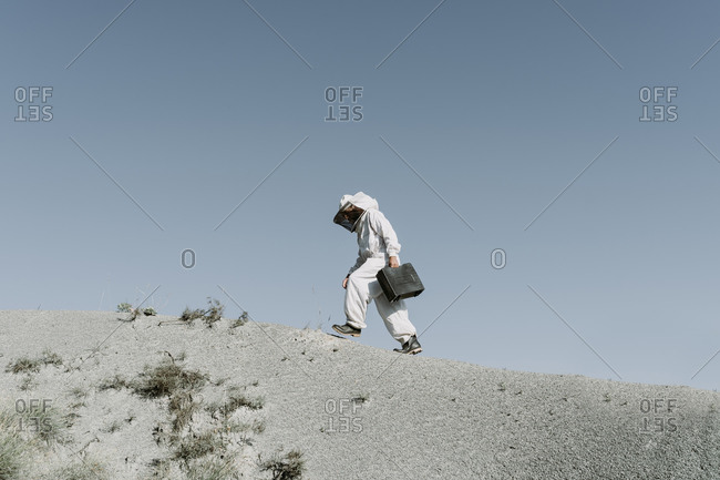 Man with briefcase wearing a beekeeper dress walking in a dry apocalyptical landscape