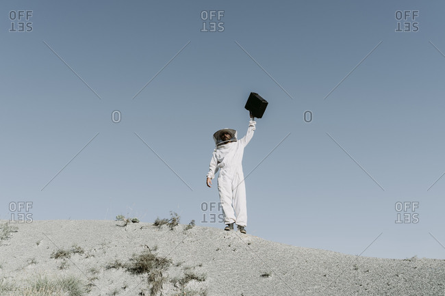 Man wearing a beekeeper dress holding up briefcase in a dry apocalyptical landscape