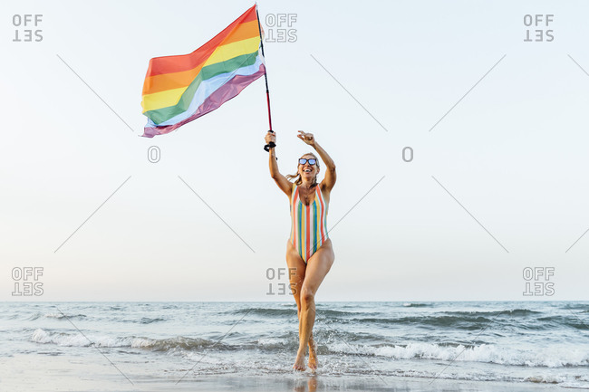 Mature woman running on the beach with gay pride flag