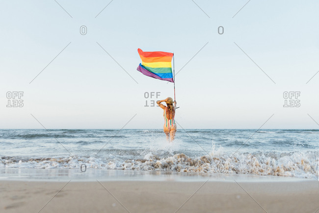 Mature woman on the beach with gay pride flag- rear view
