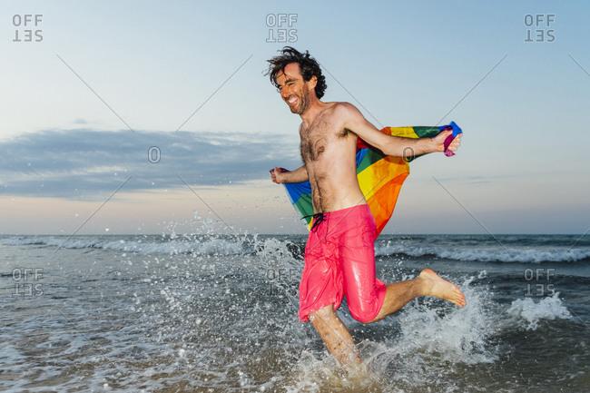 Laughing man running in splashing water- carrying gay pride flag