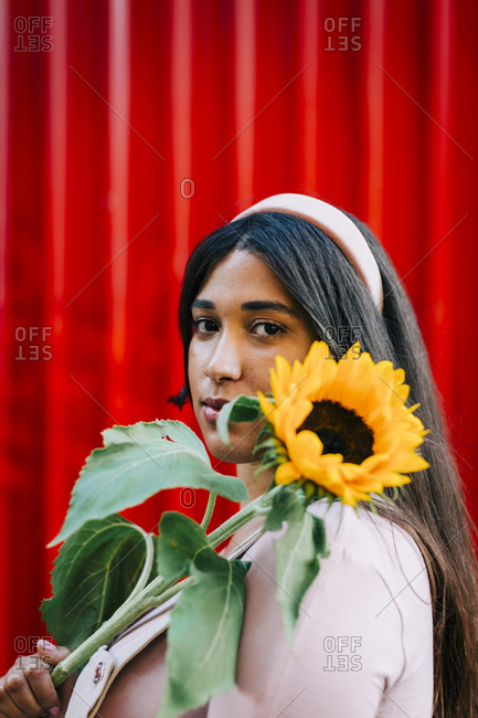 Young woman in front of red wall- holding sunflower