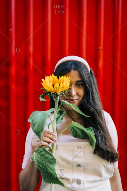 Young woman in front of red wall- covering eye with sunflower