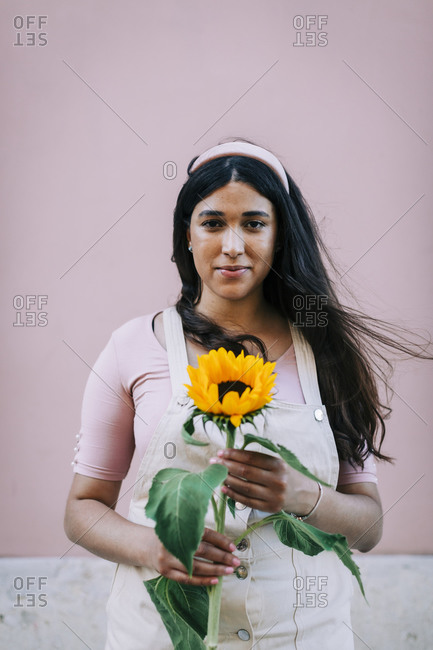Young woman in front of pink wall- holding sunflower
