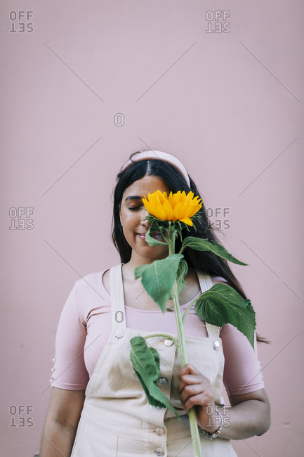 Young woman in front of pink wall- covering eye with  sunflower