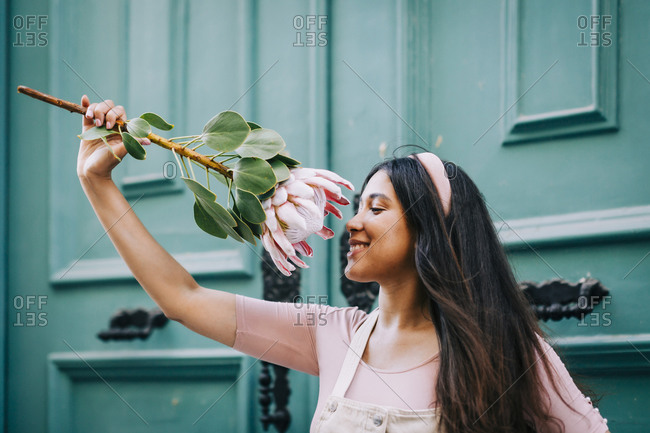 Smiling woman smelling protea flower in front of green door