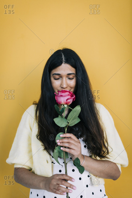 Young woman in front of yellow wall smelling rose