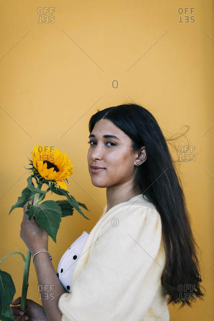 Young woman in front of yellow wall holding sunflower