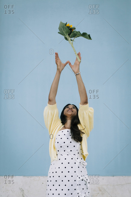 Young woman in polka dot dress throwing sunflower