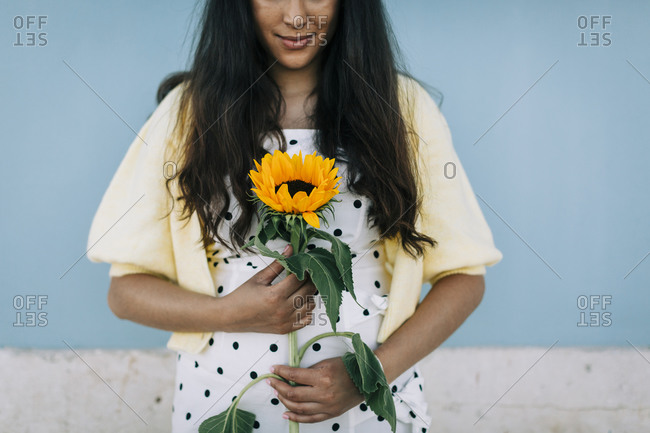 Young woman in polka dot dress holding sunflower