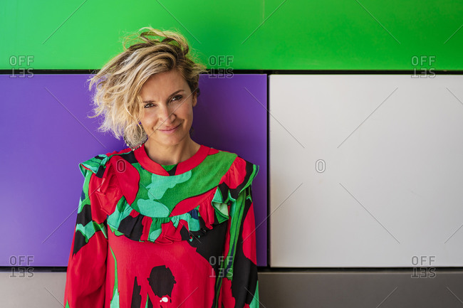 Female cook in casual standing against colorful wall