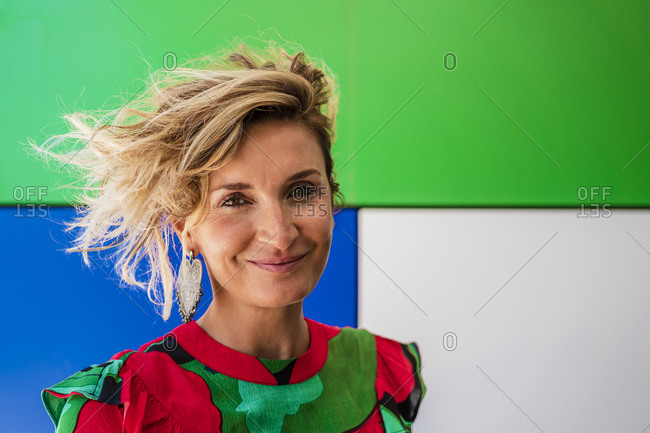 Confident female cook with short blond hair against colorful wall
