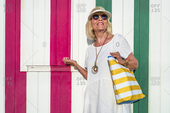 Fashionable senior woman with eye shield and sunglasses standing in front of colorful striped wall