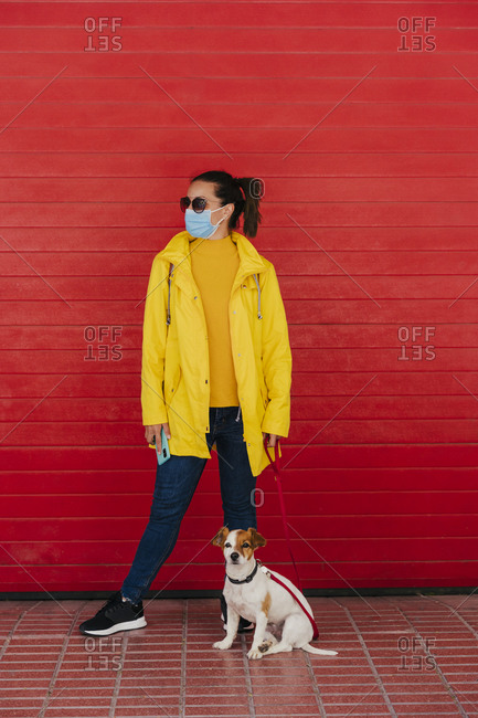 Woman with face mask and dog- wearing yellow raincoat in front of red wall