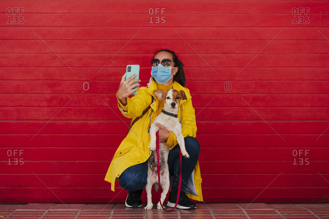 Woman with face mask and dog- taking smartphone selfies in front of red wall