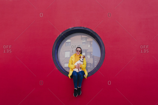Woman in yellow raincoat sitting in porthole in red wall- with dog on lap