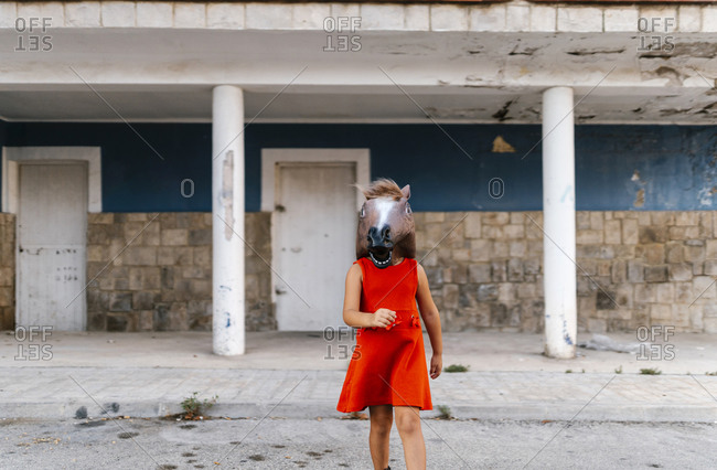 Little girl with a horse's head and a red dress walking away from an abandoned house