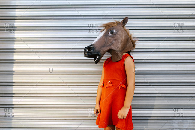 Little girl with a horse's head and a red dress in front of  metal shutter