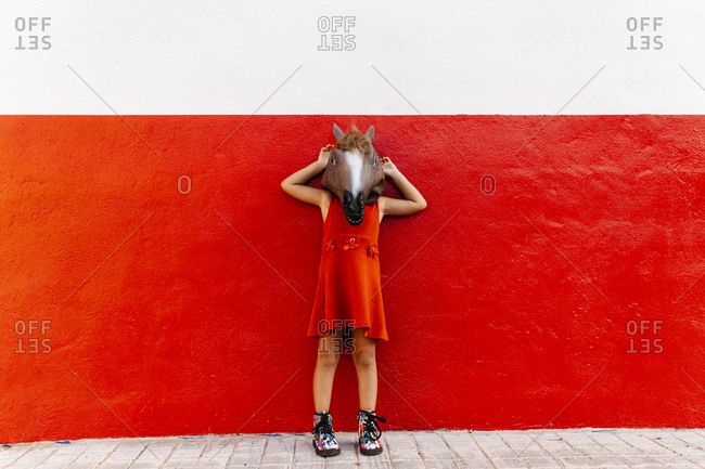 Little girl with a horse's head and a red dress leaning on a red and white wall