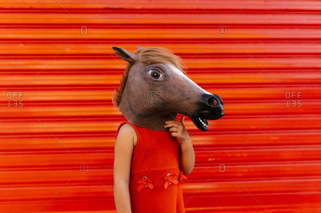 Little girl with a horse's head and a red dress standing in front of red roller shutter