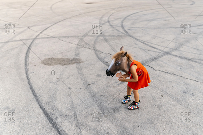 Little girl with a horse's head and a red dress- standing on asphalt with tire tracks