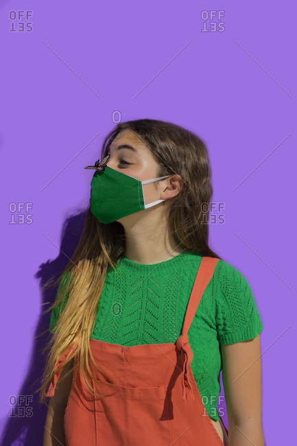 Teenage girl wearing protective face mask looking at fly sticker on nose