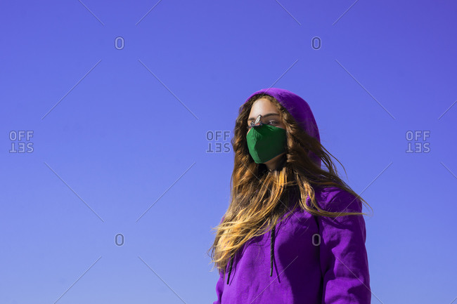 Teenage girl wearing hoodie and protective face mask with fly sticker on nose