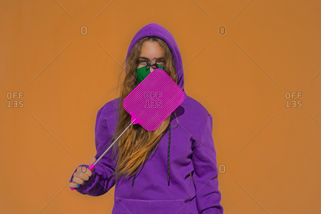 Teenage girl wearing protective face mask with fly sticker- holding swatter