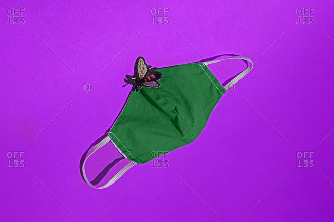 Fly sticker on green protective face mask against pink background