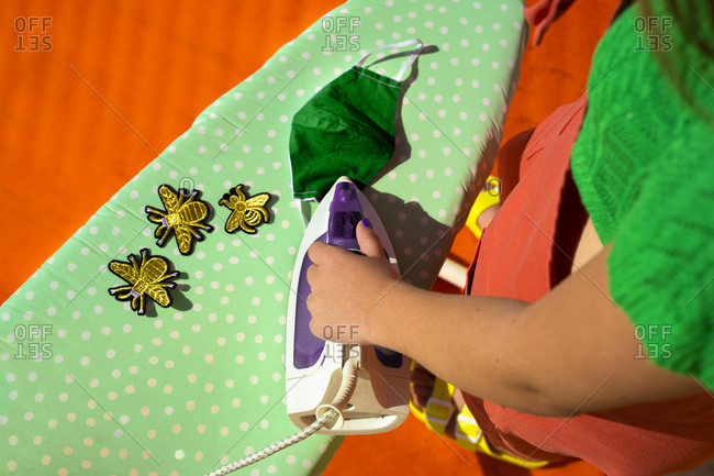 Teenage girl ironing bee patches on green protective mask