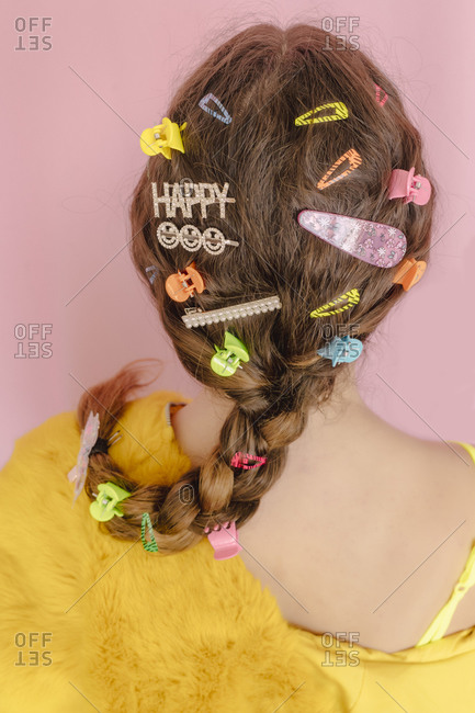 Teenage girl with various hair pins in her braid- rear view