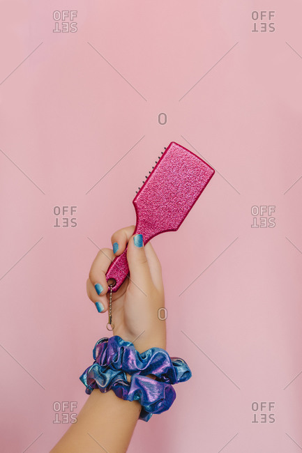 Hand of teenage girl holding pink hair brush