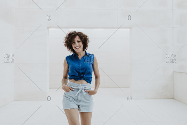 Cheerful woman with curly hair standing on floor against tiled wall