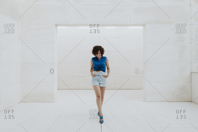 Stylish woman with curly hair walking on tiled floor against wall