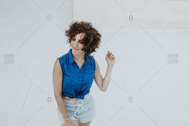 Smiling woman with eyes closed standing on floor against tiled wall