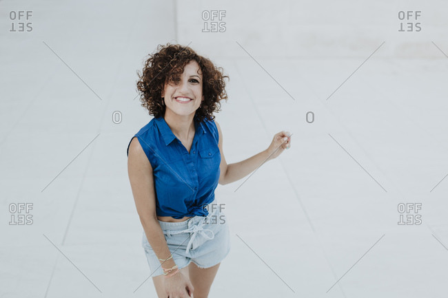 Smiling woman with curly hair standing on floor against tiled wall