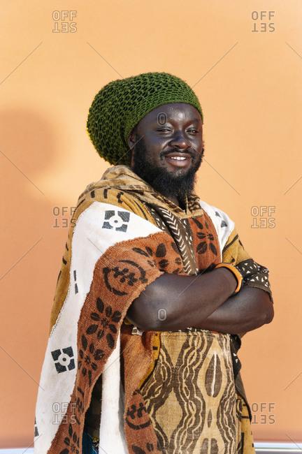 Portrait of Rastafai man with dreadlock cap against orange background
