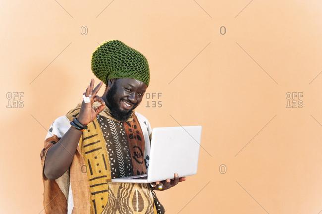 Portrait of Rastafai man with dreadlock cap using laptop- making positive hand sign