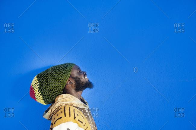 Portrait of Rastafai man with dreadlock cap against blue background