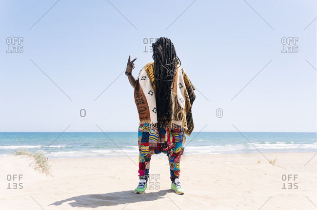 Man standing on beach with dreadlocks hiding his face- making rude hand sign