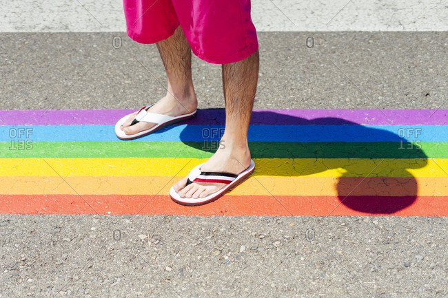 Man standing on rainbow color crosswalk