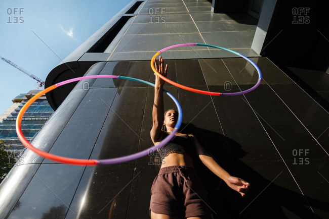 Sporty woman juggling plastic hoops outside modern building in city