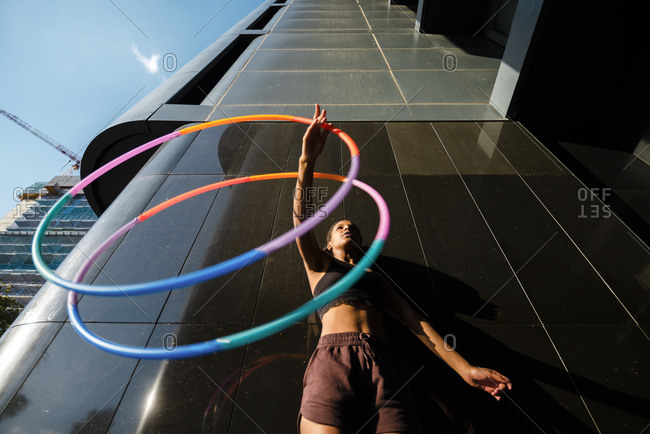 Sporty woman exercising with plastic hoops outside modern building